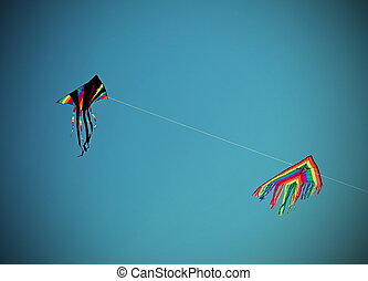 Two huge kites fly in the blue sky - big kites fly high in...
