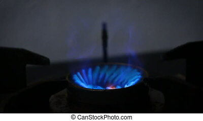 Close up shot start ignition burning gas stove and blue fire with dark and grain processed