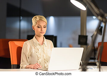 woman working on laptop in night startup office - young...