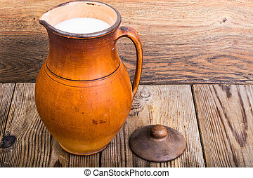 Vintage clay pitchers on wooden background