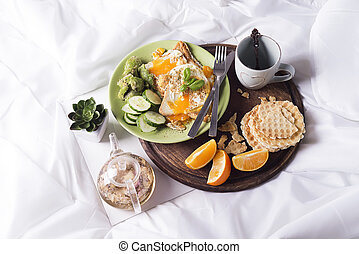 Fried eggs with toasts and tea in bed - Concept of breakfast...