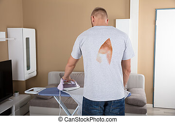 Rear View Of A Man Ironing Cloth - Rear View Of A Man...