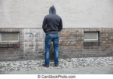 Man In Hood Peeing On Wall - Rear View Of A Man In Hood...