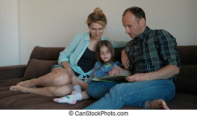 Husband, wife and child together read a book on the couch....