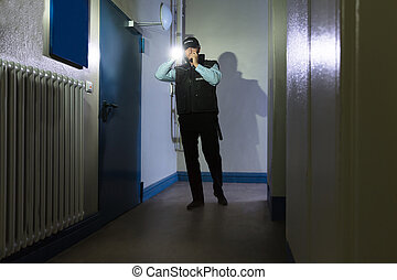 Security Guard With Flashlight Standing In Corridor