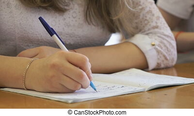 Student writing text in exercise book. Close-up - Student...