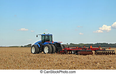 Blue Tractor - Blue farm tractor pulling a plow in a farm...