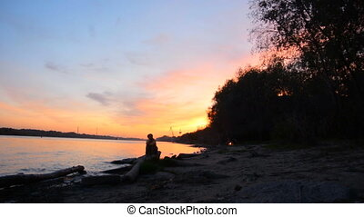 Silhouette of a woman sitting on the river bank, beautiful...