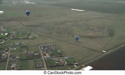 Hot air balloon aerial view on field and cottages - Hot air...