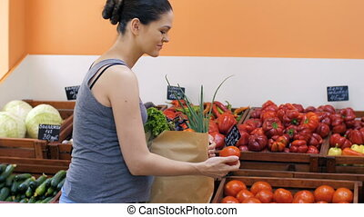 Pregnant Woman Buying Vegetables - Young pregnant woman at...