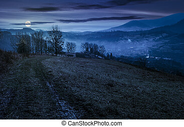 dirt road to village down the hill at night - dirt road to...
