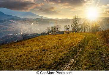 dirt road to village down the hill at sunset - dirt road to...