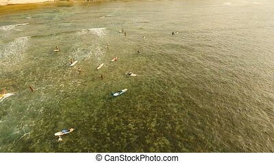 Aerial view surfers on the waves.Siargao, Philippines. Cloud...