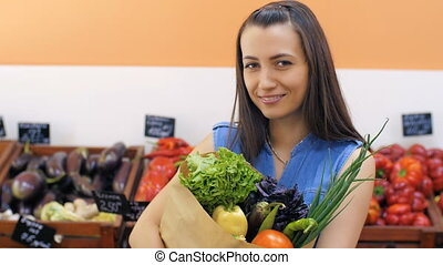 Smiling Woman With Bag of Products - Young woman at the...