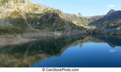 Mountains reflect on lake Gemelli basin on the Bergamo Alps,...