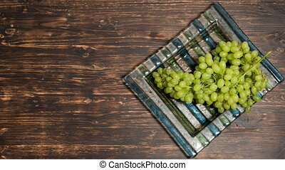 Bunch of grapes lying on a plate, top view