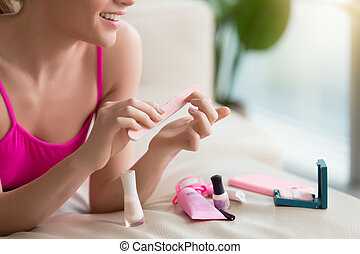 Woman using nail buffer when doing manicure - Close up image...