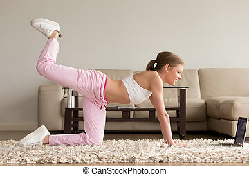 Woman doing one knee kickback exercise at home - Pretty...