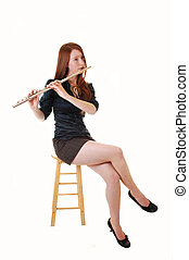 Girl playing flute. - A young woman with long red hair...