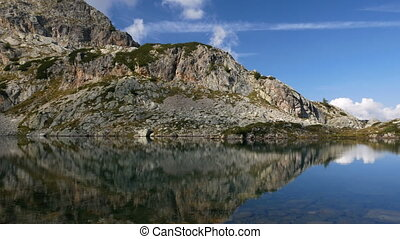 Mountains reflect on small alpine lake on the Bergamo Alps,...