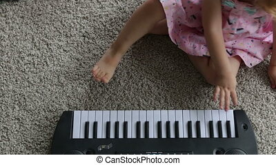 Child little girl playing on a toy piano. Full HD video -...