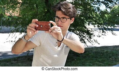 Young man taking photos with cell phone - Handsome young man...