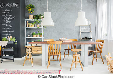 Wooden table and chalkboard wall in stylish dining room...