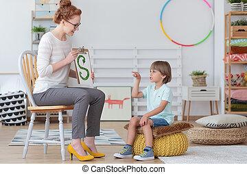 Boy practicing correct pronunciation - Boy sitting on yellow...