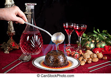 Christmas pudding flambe - Hand serving burning brandy over...