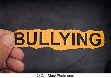 Person holds piece of paper with word Bullying in his hand
