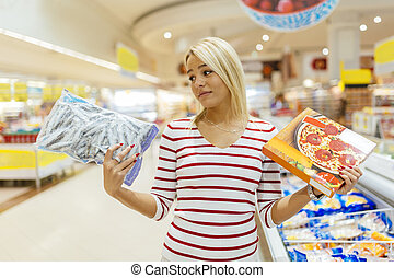Beautiful woman deciding on what to buy