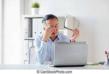tired businessman with glasses at laptop in office -...