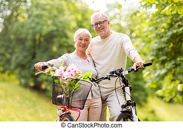 happy senior couple with bicycles at summer park - old age,...