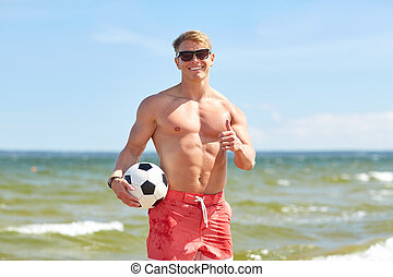young man with soccer ball on beach