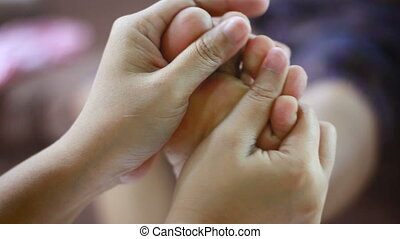Hands of young woman gently touch massage to foot of old...
