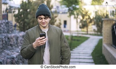 Young black haired guy web surfing in a park - Close up of a...
