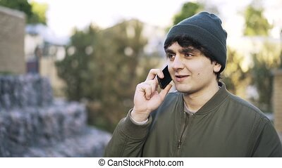 Close up of a young man in a beanie talking on phone outside...