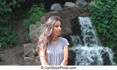 Beautiful young woman posing against a waterfall background....