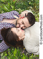 A loving couple of hipsters lay on the grass