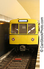 Yellow metro car stationed at the underground train station...