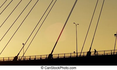 Aerial shot of silhouettes of cyclists on the guyed bridge -...