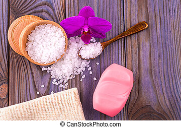 White bath salt in a wooden cup with a spoon on a wooden...