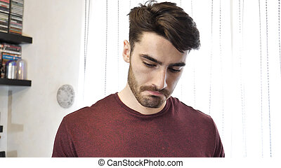 Young Man Looking Down Sad with Pouting Lips - Young...