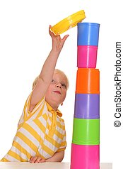 Child builds stacking tower - Young boy has build a funny...