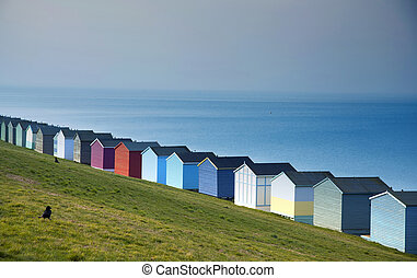 Blue sky and colorful beach huts along the coastline of Whitstable