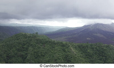 Fog and clouds over a volcano and an lake Gunung-Batur or...
