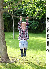 Young boy plays in the garden - Happy young boy plays in the...
