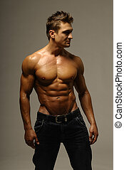 Young Strong Man - An attractive strong man posing in jeans