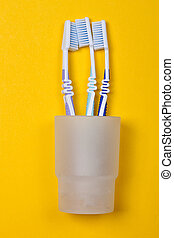 three toothbrushes in a glass on the yellow background. Top...