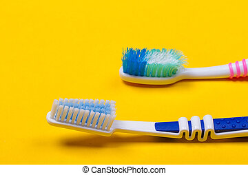 Toothbrushes on yellow background - Old used and new...